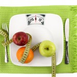 Diet concept. Fruits with measuring tape  on a plate like weight